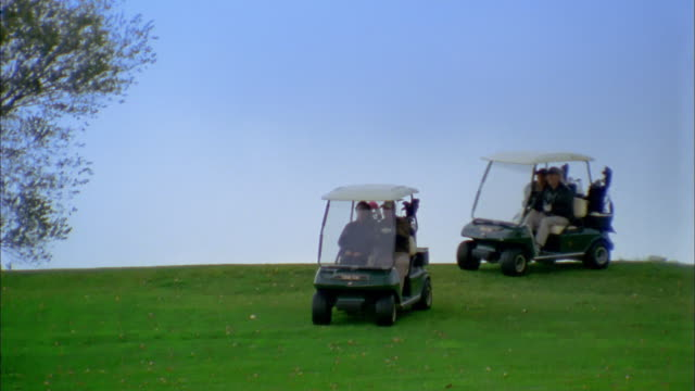 wide shot pan couples driving golf carts down hill on golf course - golf cart stock videos and b-roll footage
