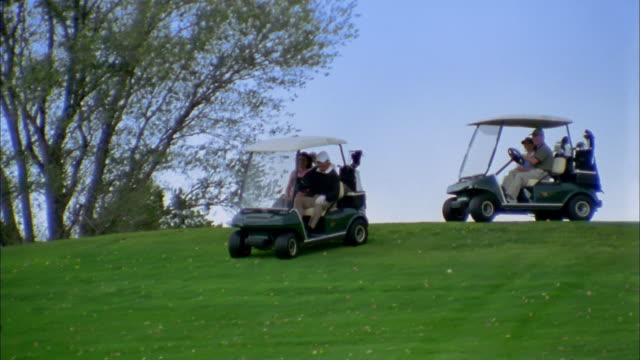 wide shot pan couples driving golf carts down hill on golf course - golf cart stock videos & royalty-free footage