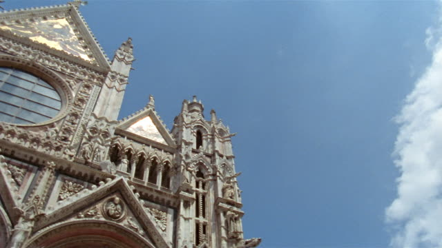 vidéos et rushes de wide shot pan detail of front fa?ade of the duomo in siena / tuscany, italy - fronton