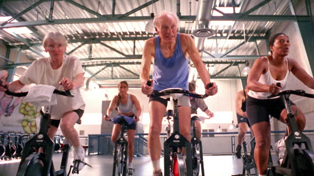 Wide shot pan dolly shot people riding exercising bicycles during exercise class at gymnasium with instructor in foreground