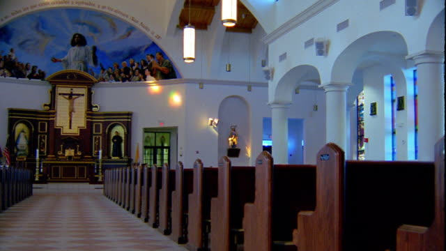 wide shot pan empty church with wooden pews and crucifix altar - altar stock videos & royalty-free footage