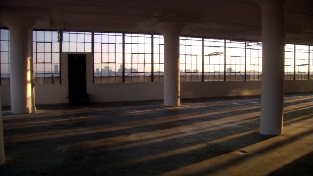 wide shot pan empty loft with pillars and sunlight at dusk / nyc - loft stock videos and b-roll footage