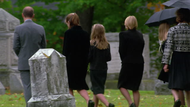wide shot pan extended family visiting grave in cemetery / vermont - mourning stock videos & royalty-free footage
