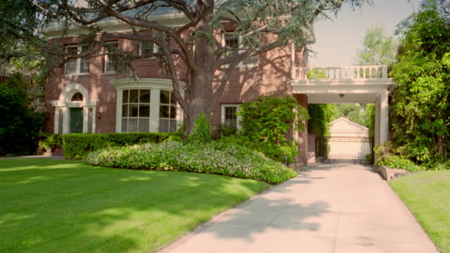 Wide shot pan exterior view of brick house with bushes and large tree in front yard