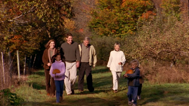wide shot pan family walking through field in the country / boys and girl running + carrying pumpkins - adoption stock videos & royalty-free footage
