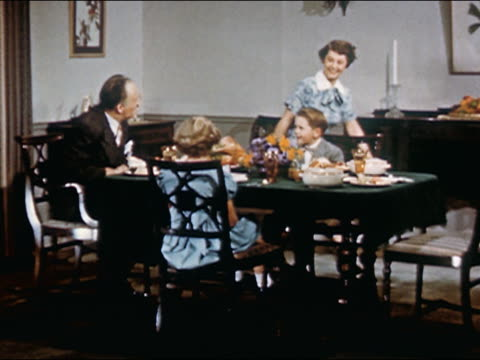 1951 Wide shot pan family with 2 small children eat turkey dinner in dining room wearing Sunday best / AUDIO