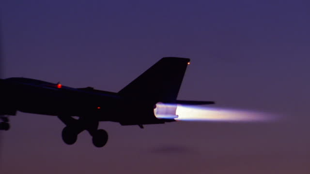 Wide shot pan fighter jet taking off at dusk