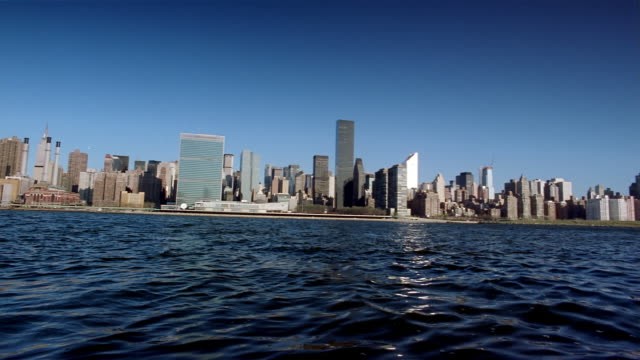 wide shot pan from right to left view across east river of manhattan skyline / new york city - citigroup center manhattan stock videos & royalty-free footage