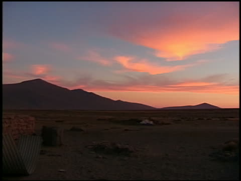 wide shot pan from stone house to rocky landscape at sunset / peru - stone house stock videos & royalty-free footage