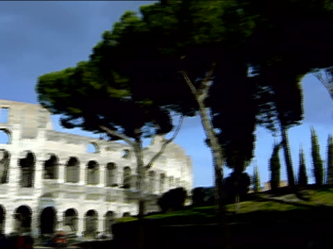 Wide shot pan from trees to exterior view of Coliseum / Rome, Italy