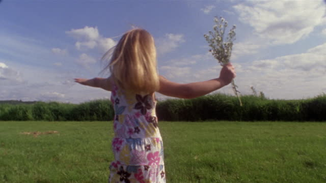 vidéos et rushes de wide shot pan girl runing in field and holding bunch of flowers / des moines, king county, washington, usa - cheveux blonds