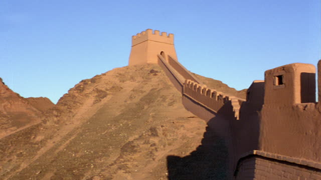 wide shot pan great wall of china on barren mountain with guard tower at peak / gobi desert, china - great wall of china stock videos & royalty-free footage