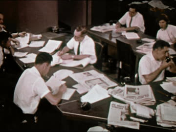 vidéos et rushes de 1964 wide shot pan group of men and women working on phones in busy newsroom at new york newsday / long island, new york / audio - new york newsday
