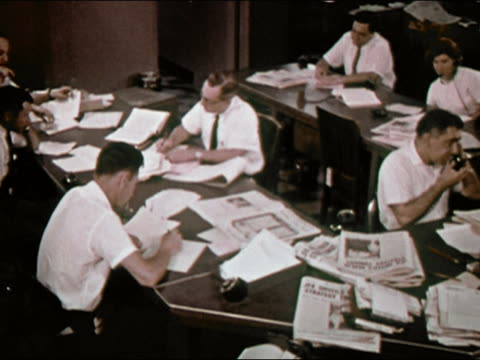 vídeos de stock e filmes b-roll de 1964 wide shot pan group of men and women working on phones in busy newsroom at new york newsday / long island, new york / audio - sala de imprensa