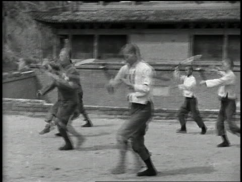 vídeos de stock e filmes b-roll de 1932 wide shot pan group of men practice martial art with swords - artes marciais