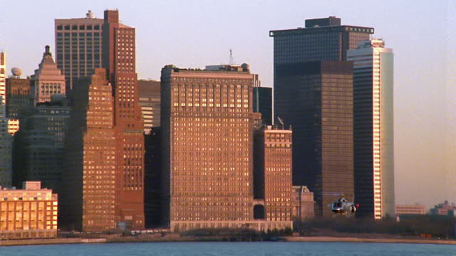 wide shot pan helicopter flying past buildings and over east river in lower manhattan / new york - anno 1990 video stock e b–roll