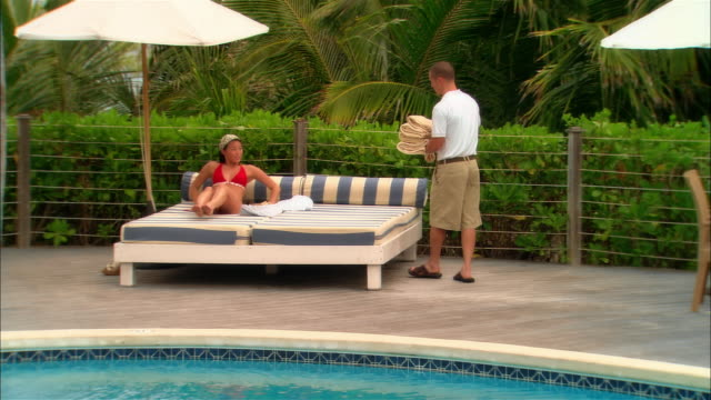 wide shot pan hotel worker walking alongside pool and handing towel to woman sitting on lounge chair/ harbour island, bahamas - grooming product stock videos & royalty-free footage