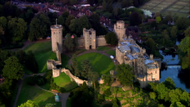 vidéos et rushes de wide shot pan houses surrounding warwick castle on bank of avon river/ warwick, warwickshire, england - xième siècle