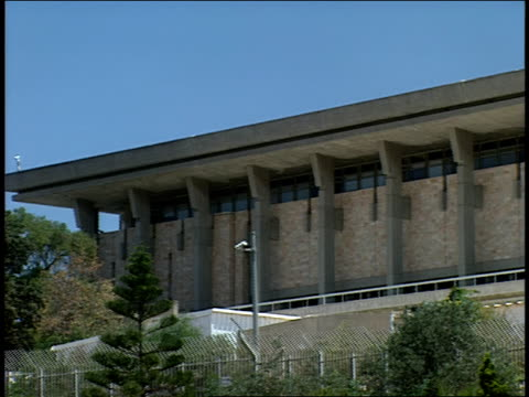 2006 Wide shot pan Israeli flag waving above Knesset building, house of Israel's legislature/ Jerusalem, Israel