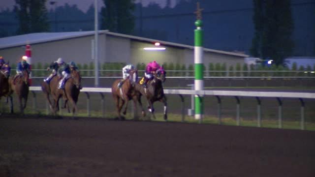 1996 wide shot pan jockeys on horses racing on track / Seattle, Washington