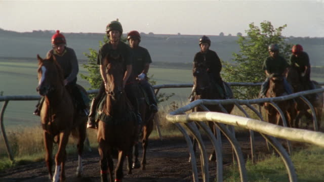 vidéos et rushes de wide shot pan jockeys riding horses on dirt track/ berkshire, england - groupe moyen d'animaux