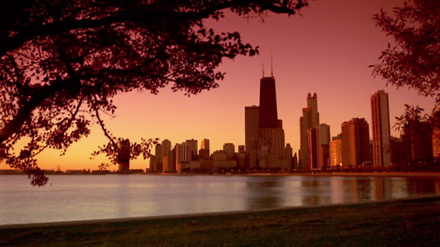 Wide shot pan Lake Michigan and Chicago skyline including Hancock Building at sunset