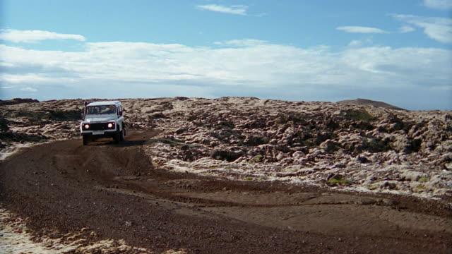 wide shot pan land rover riding through lava field near the blue lagoon (blaa loninu) / iceland - vulkanlandschaft stock-videos und b-roll-filmmaterial