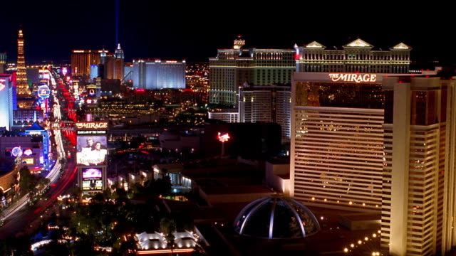 wide shot pan las vegas strip past mirage hotel with time lapse traffic at night / las vegas, nevada - the mirage las vegas stock videos & royalty-free footage