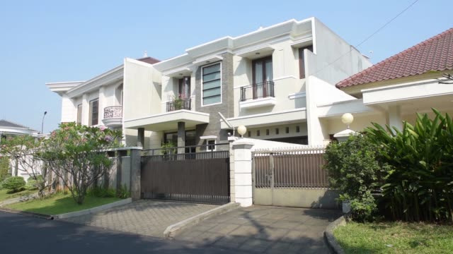 Wide shot pan left to right a car drives past houses in Jakarta Indonesia on Tuesday June 23 Wide shot pan left to right residential houses stand in...