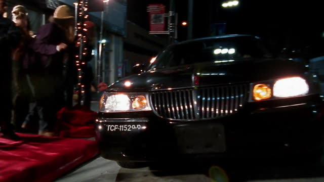 Wide shot pan limo pulling up to red carpet / groupies and press mobbing vehicle