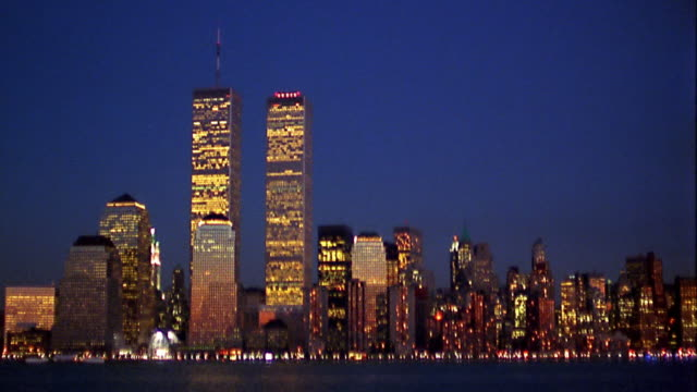 wide shot pan lit lower manhattan skyline with world trade center at dusk / harbor in foreground / helicopter passes - world trade center manhattan video stock e b–roll