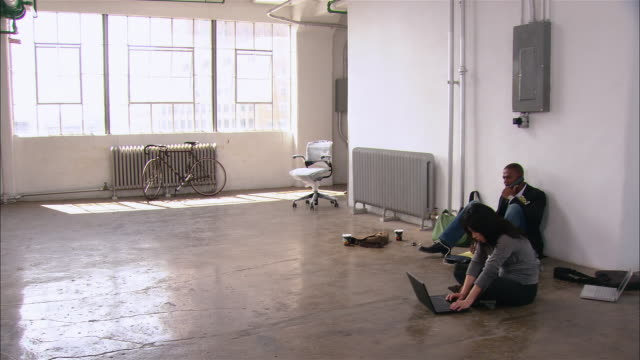 Wide shot pan man and woman sitting on floor of empty loft space/ man pushing new chair into space/ woman entering and looking at chair/ Brooklyn, New York