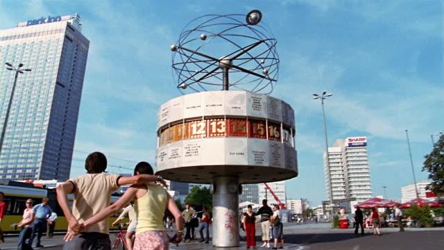 vídeos de stock, filmes e b-roll de wide shot pan man and woman walking near the atomic clock / berlin, germany - de braços dados
