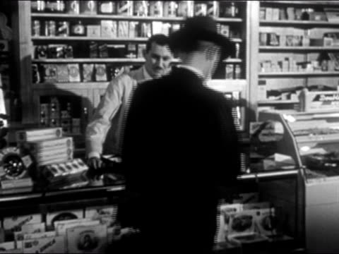 1948 wide shot pan man in suit buying cigarettes and sitting down at lunch counter - cigarette stock videos & royalty-free footage