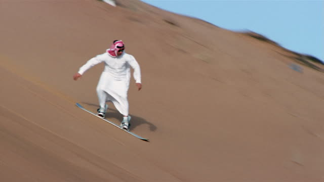 wide shot pan man in traditional middle eastern clothing sandboarding down dune/ dubai - sand dune stock videos and b-roll footage