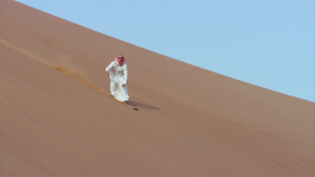 Wide shot pan man in traditional Middle Eastern clothing sandboarding down dune and falling/ Dubai