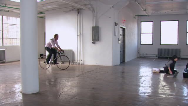 Wide shot pan man riding bicycle into empty loft space to meet man and woman sitting on floor/ man on bike high-fiving man on floor and kissing woman on cheek/ Brooklyn, New York