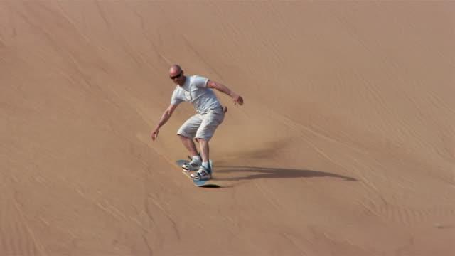 vídeos de stock, filmes e b-roll de wide shot pan man sandboarding down dune/ dubai - membro humano