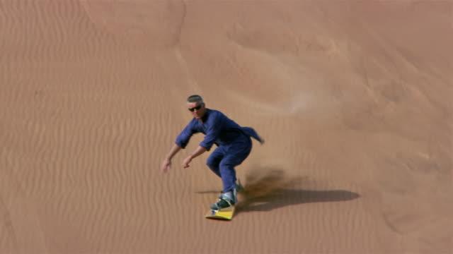 wide shot pan man sandboarding down dune/ dubai - sand dune stock videos and b-roll footage
