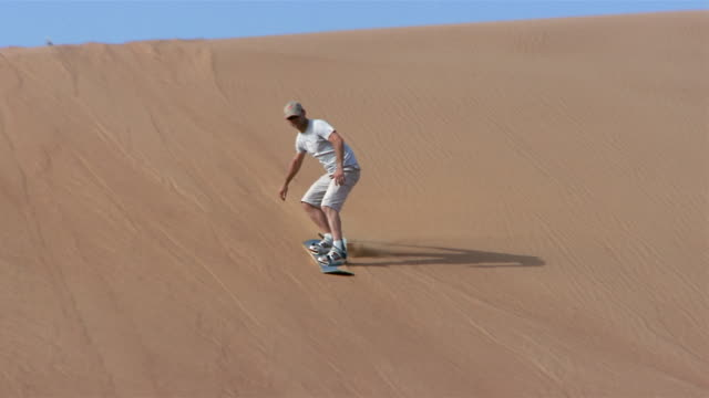 wide shot pan man sandboarding down dune/ dubai - sliding stock videos & royalty-free footage