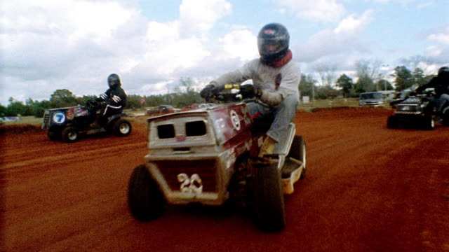 wide shot pan men wearing racing gear and riding lawn mowers on dirt track / alabama - tagliaerba video stock e b–roll