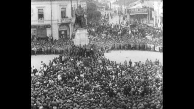 wide shot pan of romanian civilians gathered in iasi union square dancing cheering waving / tighter street level shot of civilians packed into the... - 停戦点の映像素材/bロール