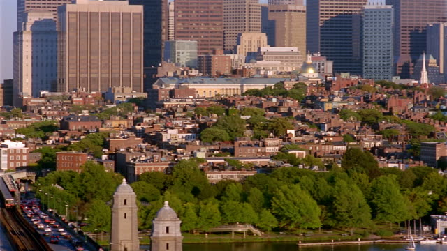 Wide shot pan of skyline from Longfellow Bridge with Charles River in foreground / Boston