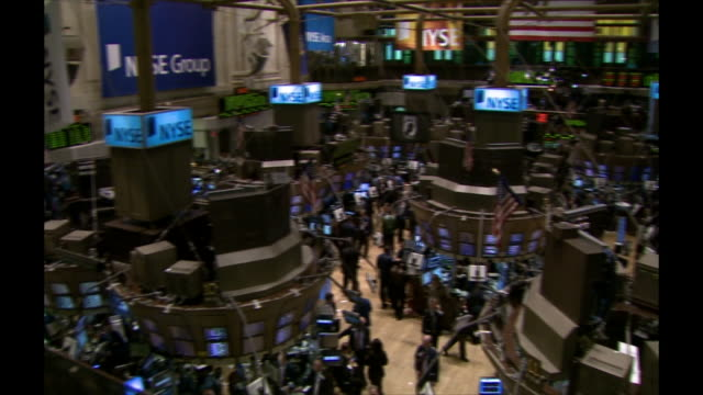 Wide shot pan of the New York Stock Exchange trading floor during business hours