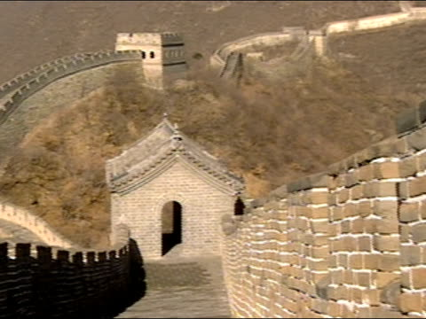 Wide shot pan of watchtower at Great Wall of China with mountains in background