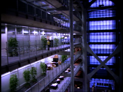 Wide shot pan office building interior w/many tiers and open atrium
