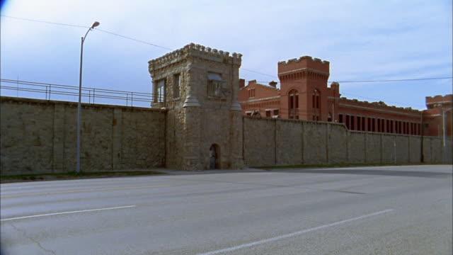 wide shot pan old fashioned prison complex - blocco stradale video stock e b–roll