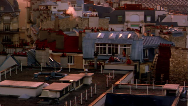 wide shot pan over building rooftops and base of eiffel tower / paris - anno 2001 video stock e b–roll