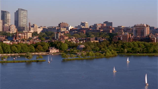 Wide shot pan over Charles River to skyline with Longfellow Bridge in foreground / Boston