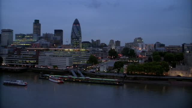 Wide shot pan over London skyline to Tower Bridge at night